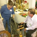 Jerry Palmer and Kathleen Barger-Hebert discussing the repair of an antique spinning wheel.